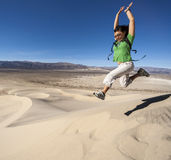 Female hiker climbing sand dunes. Royalty Free Stock Photo