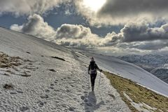 Female hiker descending a snow covered Helvellyn. Female Hiker descending Helvellyn, a mountain in The English Lake District on a Winter`s day with snow Royalty Free Stock Photos