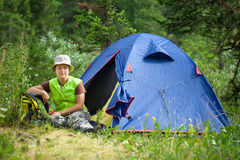 Female hiker in front of camp tent Stock Image