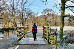Female Hiker Frosty Winter Morning. Female hiker standing on a bridge on a frosty cold winter morning in Langdale, English Lake District stock image