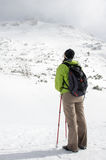 Female hiker gaze at mountain peak covered in snow Royalty Free Stock Image