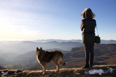 Female hiker and his dog looking horizon from ligurian apennines. In a sunny day Royalty Free Stock Photos