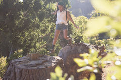 Female hiker jumping from tree stumps in forest. Young female hiker jumping from tree stumps in forest on sunny day Stock Photography