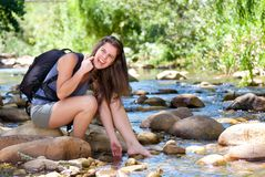 Female hiker laughing and relaxing with feet in a creek Stock Photography