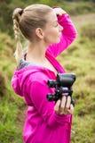 Female hiker looking away and holding binoculars Stock Photos