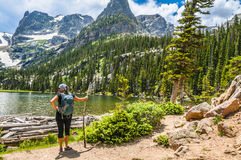 Female Hiker looking at Odessa Lake. Young attractive female enjoying stunning view at lake Odessa with notchtop peak in rocky mountain national park colorado royalty free stock photo