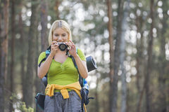 Female hiker photographing through digital camera in forest Stock Photography