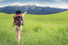 Female hiker pointing at the mountain Stock Photos