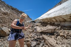 Female hiker points and smiles at a large ice cave along a trail. Of scree and talus along 20 Lakes Basin in the Eastern Sierra Nevada Mountains of California royalty free stock photography