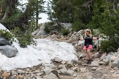 Female hiker poses next to a patch of snow still leftover on a hiking trail in the Sierra Nevada mountains of California in Little stock photos