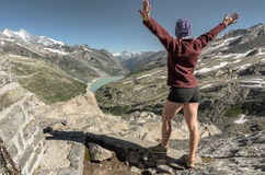 Female hiker raised her hands celebrating successful climb to to Royalty Free Stock Images