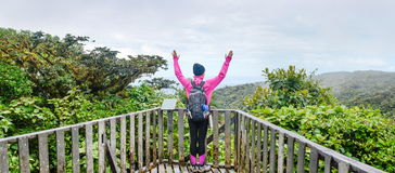 female hiker raising hands high up Stock Image