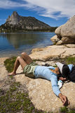 Female hiker relaxing near a lake. Royalty Free Stock Photography
