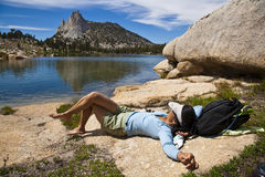 Female hiker relaxing near a lake. Stock Photo