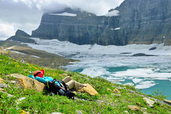 Female hiker resting by the Grinnell glacier in Many Glaciers, G Stock Photography