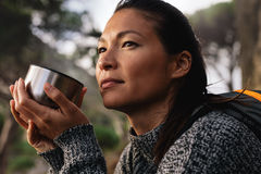 Female hiker resting outdoors with a coffee. Close up side shot of female hiker resting outdoors with a coffee and looking away. Asian woman having coffee Royalty Free Stock Photo