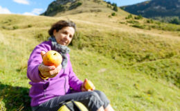 Female hiker sitting, eating an apple Royalty Free Stock Photography