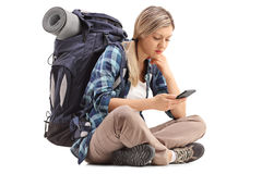 Female hiker sitting on the ground and looking at a cell phone Stock Photography