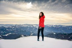 Female hiker on snow covered mountain top. Winter active lifestyle Stock Photos