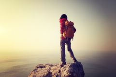 Female hiker stand on the cliff edge. At sunrise seaside Royalty Free Stock Images