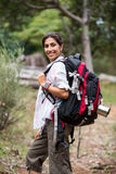 Female hiker standing in forest. Portrait of smiling female hiker standing in forest Royalty Free Stock Photo
