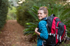 Female hiker standing in forest. Portrait of smiling female hiker standing in forest Stock Photo
