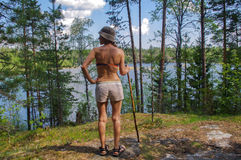 Female hiker standing on rocky trail and waching azure amazing colors mountain forest lake background Stock Photography