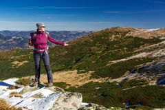 Female Hiker standing on snowy Rocks admiring scenic Winter Mountain View Stock Photography