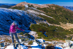 Female Hiker standing on snowy Rocks admiring scenic Winter Mountain View Stock Photo