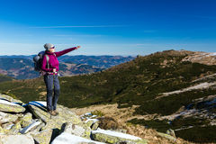Female Hiker standing on snowy Rocks admiring scenic Winter Mountain View Royalty Free Stock Image