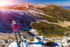 Female Hiker standing on snowy Rocks admiring scenic Winter Mountain View Sun Royalty Free Stock Photo