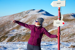 Female Hiker staying at Path Sign and admiring scenic View in Winter Mountains Royalty Free Stock Images
