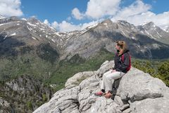 Woman sitting on cliff looking at view Royalty Free Stock Image