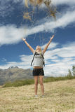 Female Hiker Throwing Grass Up In The air At Field Stock Photography