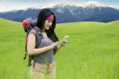 Female hiker using cellphone on the mountain Royalty Free Stock Images