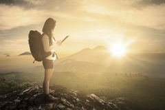 Female hiker using tablet on mountain Royalty Free Stock Image