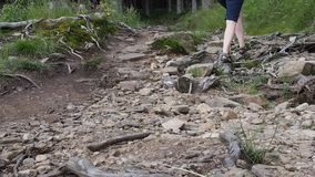 Female hiker waling on a rocky road stock video