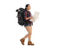 Female hiker walking and holding a generic map Royalty Free Stock Image