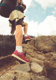 Female hiker walking through the rocky land. Royalty Free Stock Images