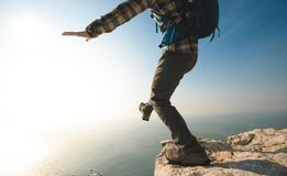 Hiker walking to the edge on sunrise seaside cliff. Female hiker walking to the edge on sunrise seae cliff Royalty Free Stock Photos