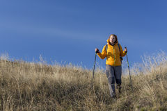 Female hiker walks downhill and enjoys warm royalty free stock images