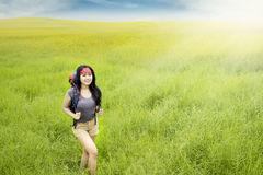 Female hiker walks on the meadow Royalty Free Stock Images