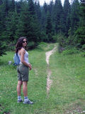 Female hiker on wooded trail. Female hiker standing along a rustic wooded trail Royalty Free Stock Image