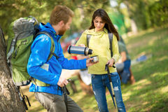 Female hikers pours water from thermos to his male friend Stock Photography
