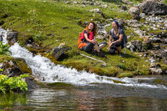 Female Hikers relaxing next to mountain river stock image