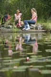 Female Hikers Resting By The Pond Stock Images