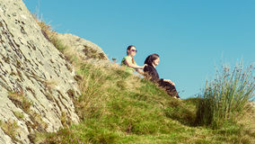 Female hikers on top of the mountain taking a break and enjoying a valley view Stock Photo