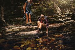 Female hikers by a water pond in mountain stock photography