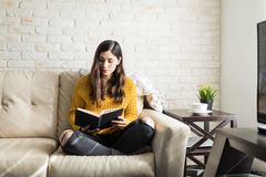 Woman Spending Leisure Time With Novel. Female hippie holding hardcover book while sitting with cross legged on couch royalty free stock image