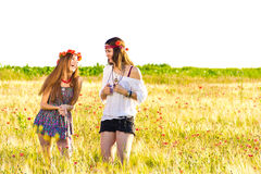 Female hippies in field. Two happy young female hippies in field with flowers in hair, white background Royalty Free Stock Photo